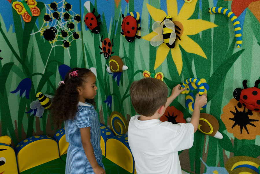 two kids decorating the classroom wall