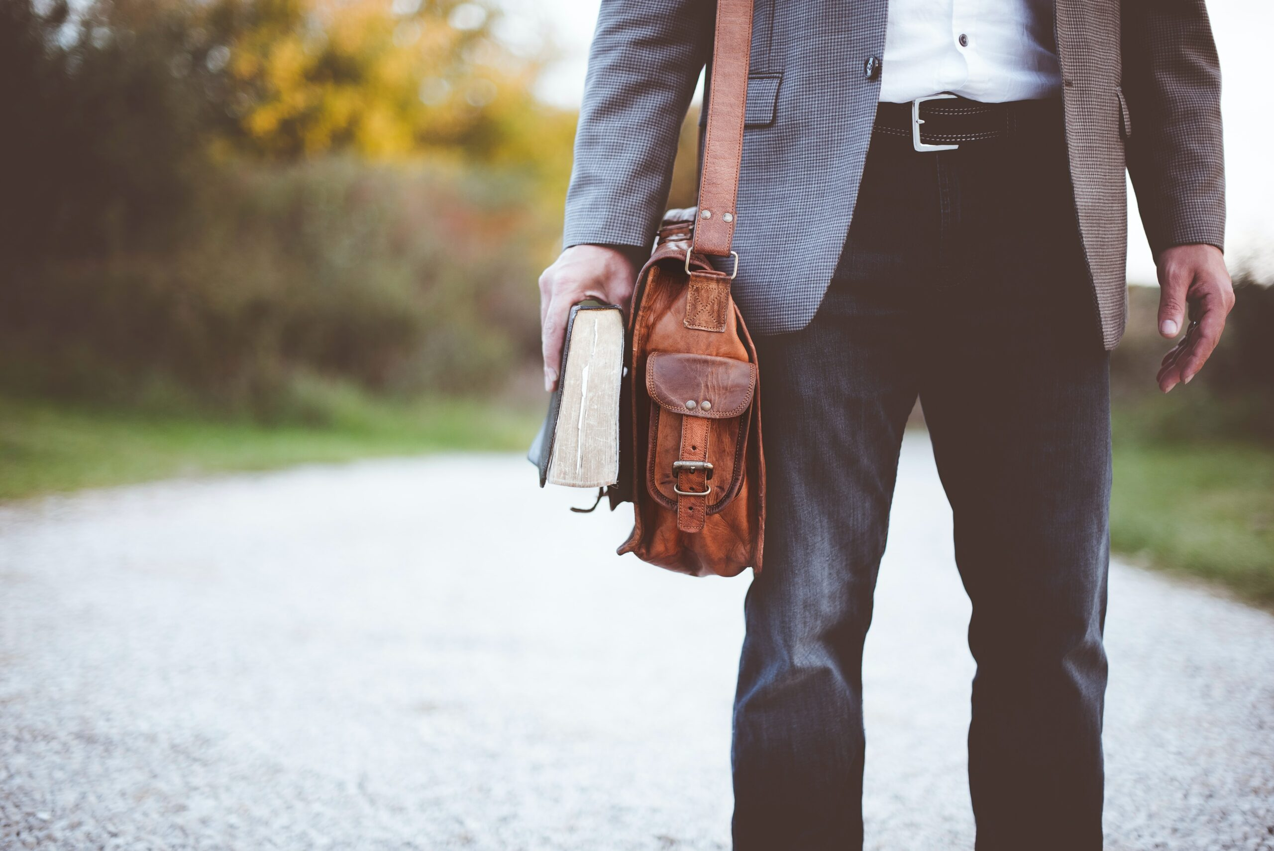 holding a book and wearing a leather bag while looking for an alternative job for teachers