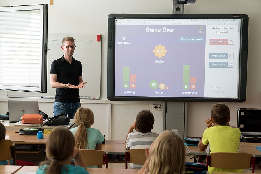 teacher in a black shirt using technology in the classroom for kids' learning