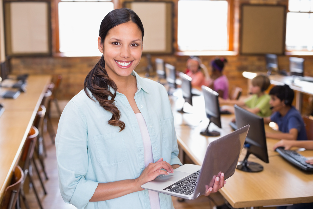 teaching smiling while holding laptop