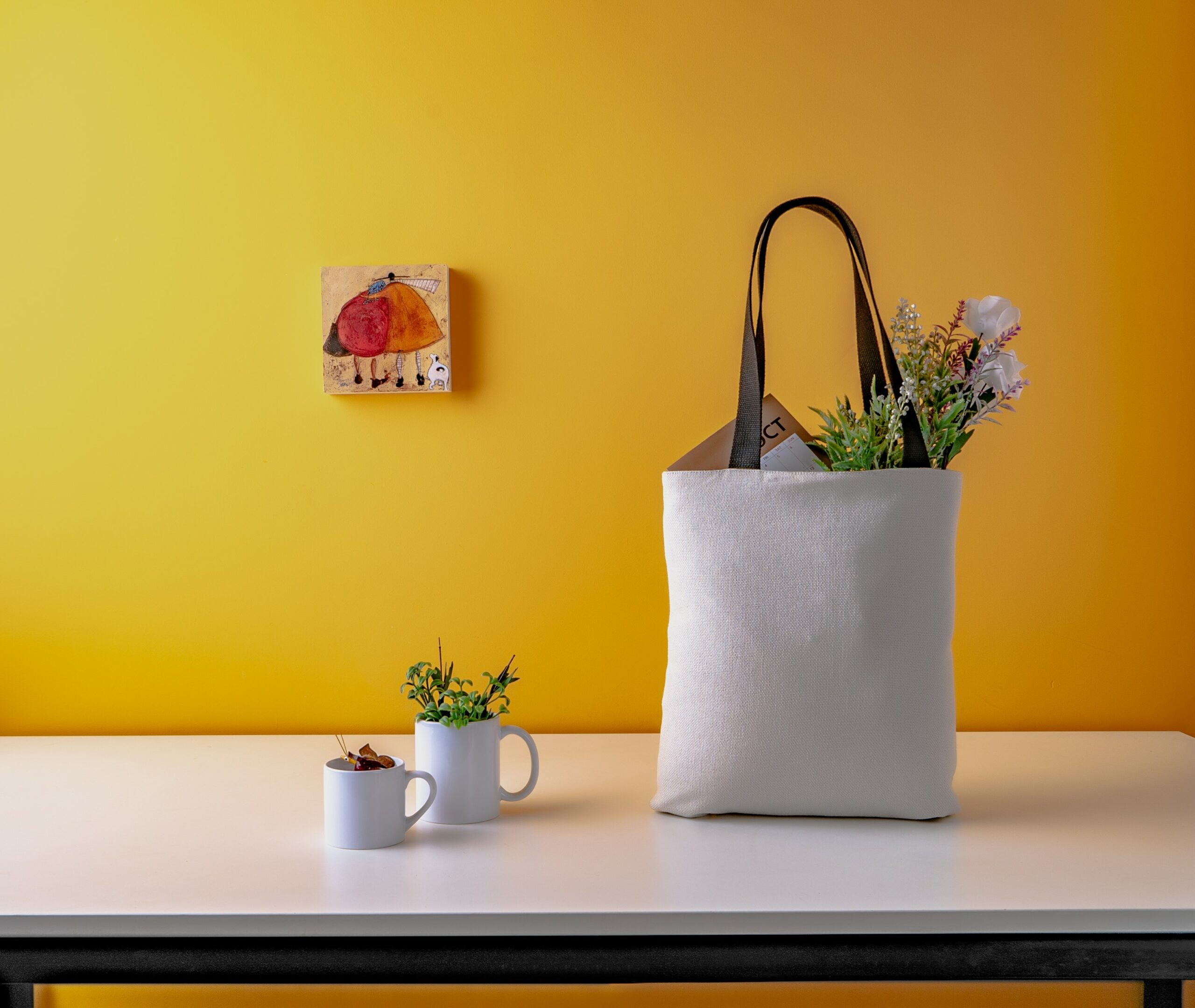 a tote bag on top of a table with flowers in it