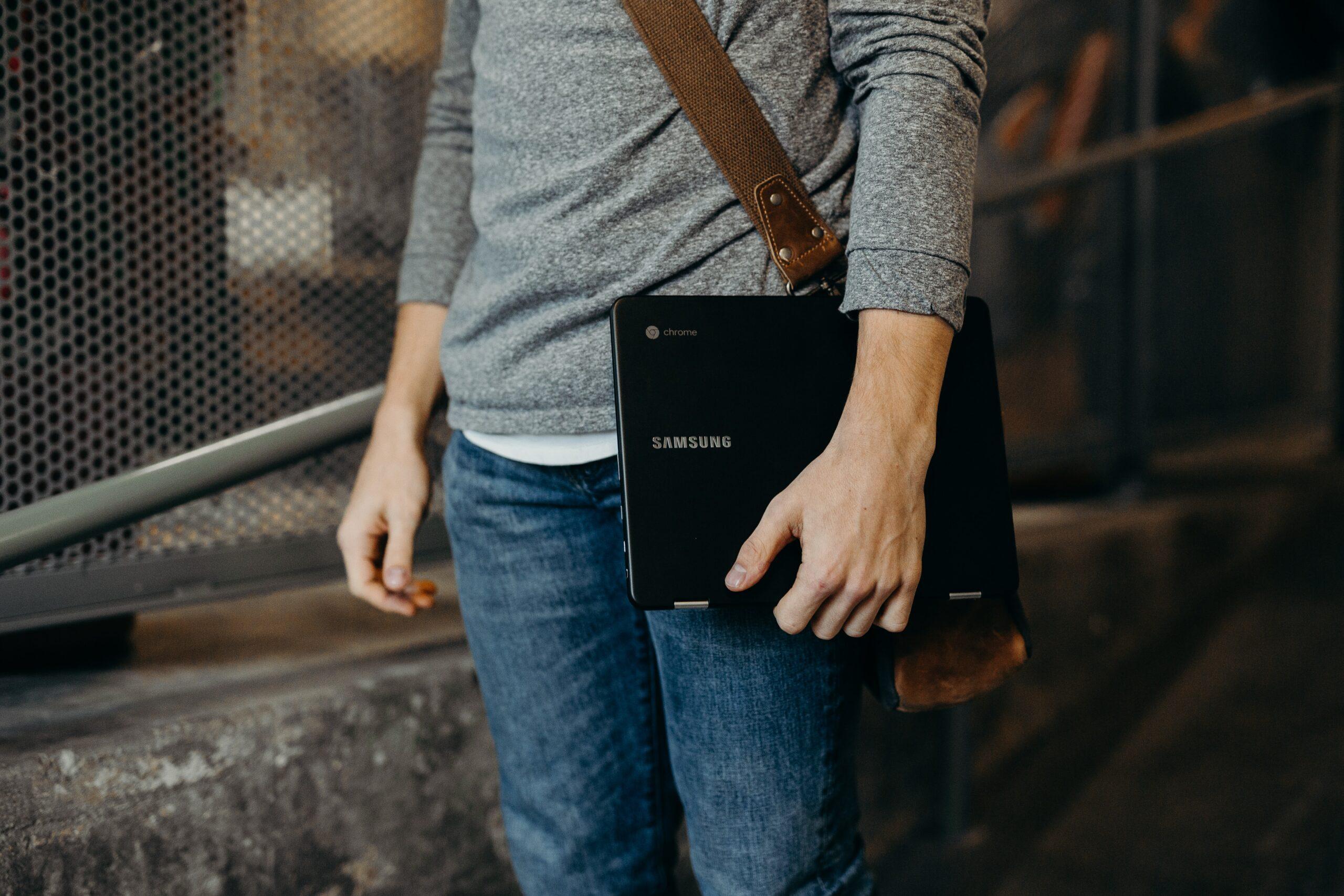 a teacher holding his chromebook effortlessly