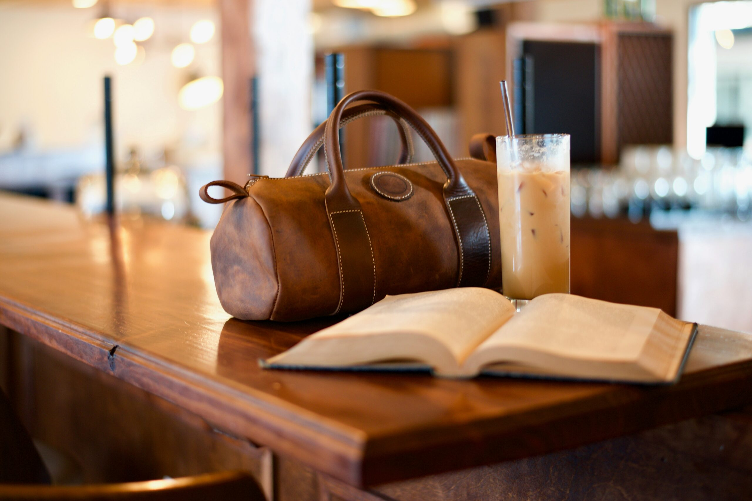 a duffle bag beside a book and iced coffee