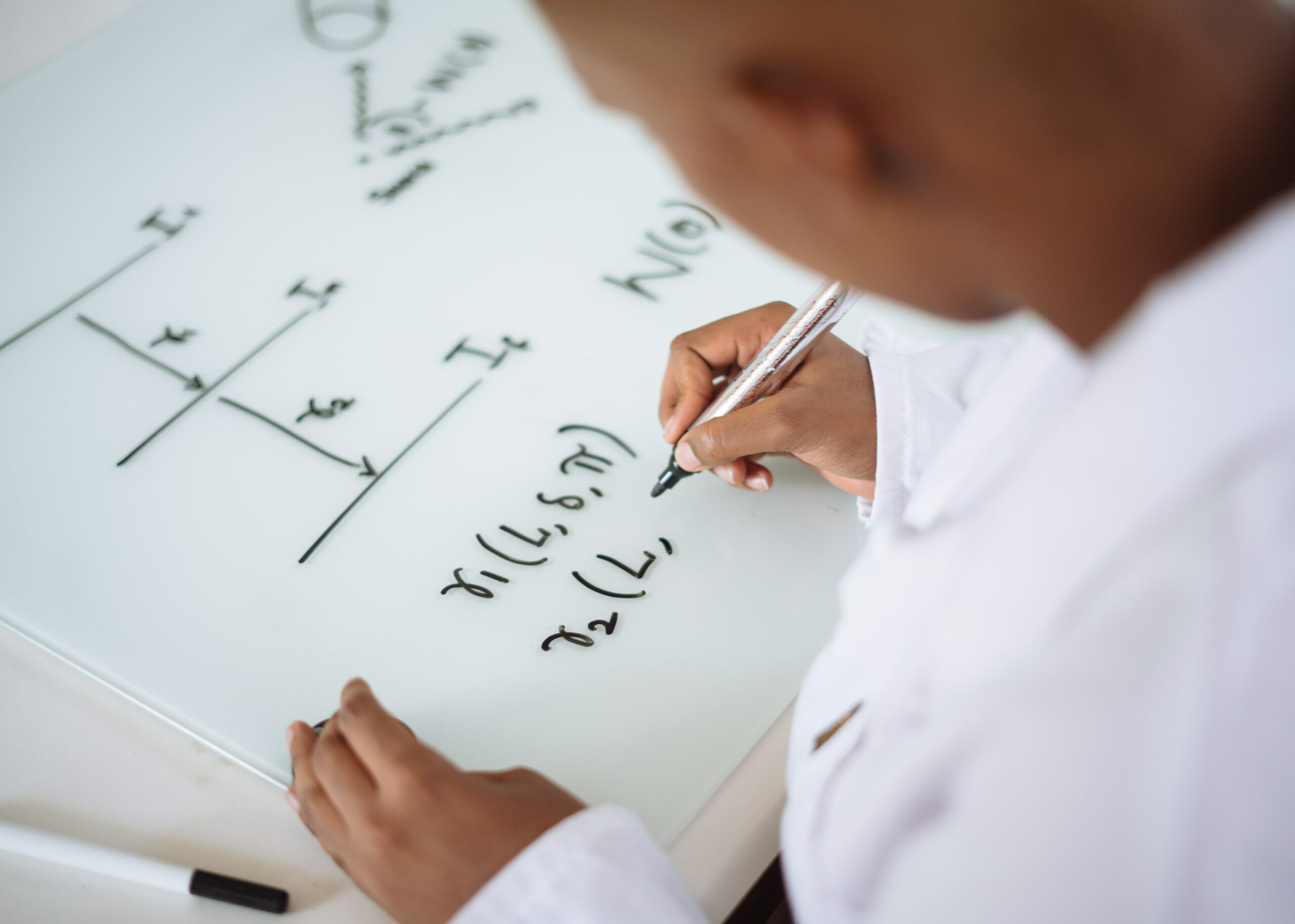 a teachers writing on his glass desk with a dry erase marker