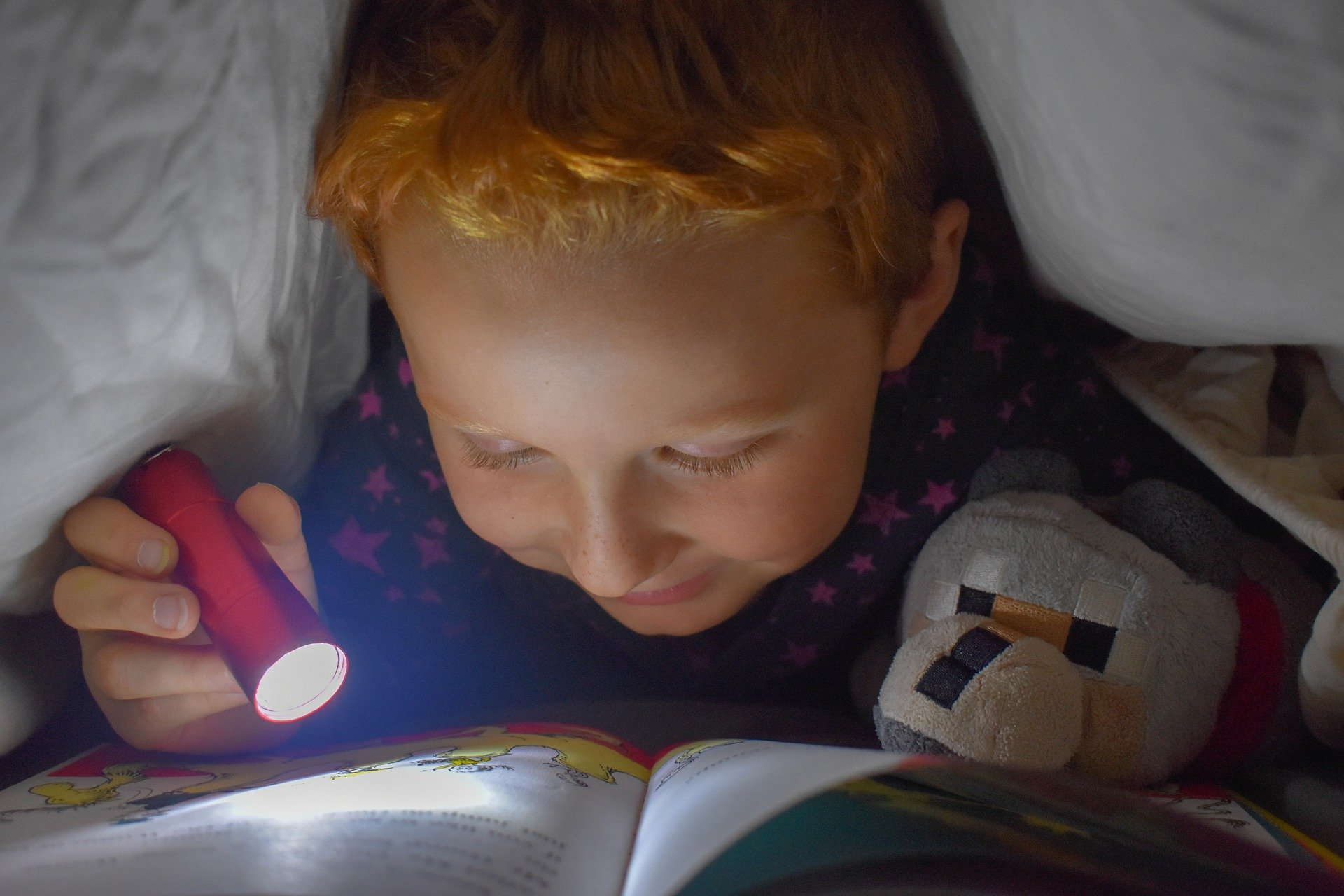 a child reading a book under his weighted blanket