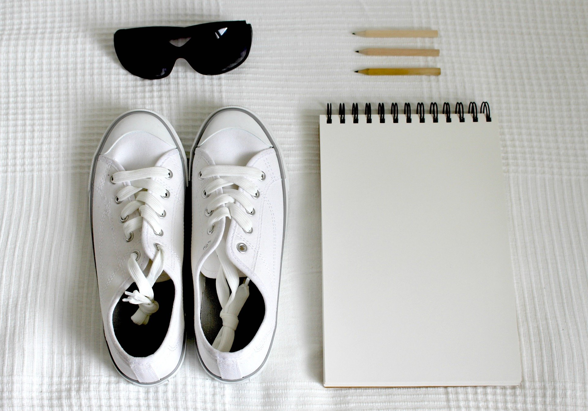 white sneakers besides a notebook and a pair of sunglasses