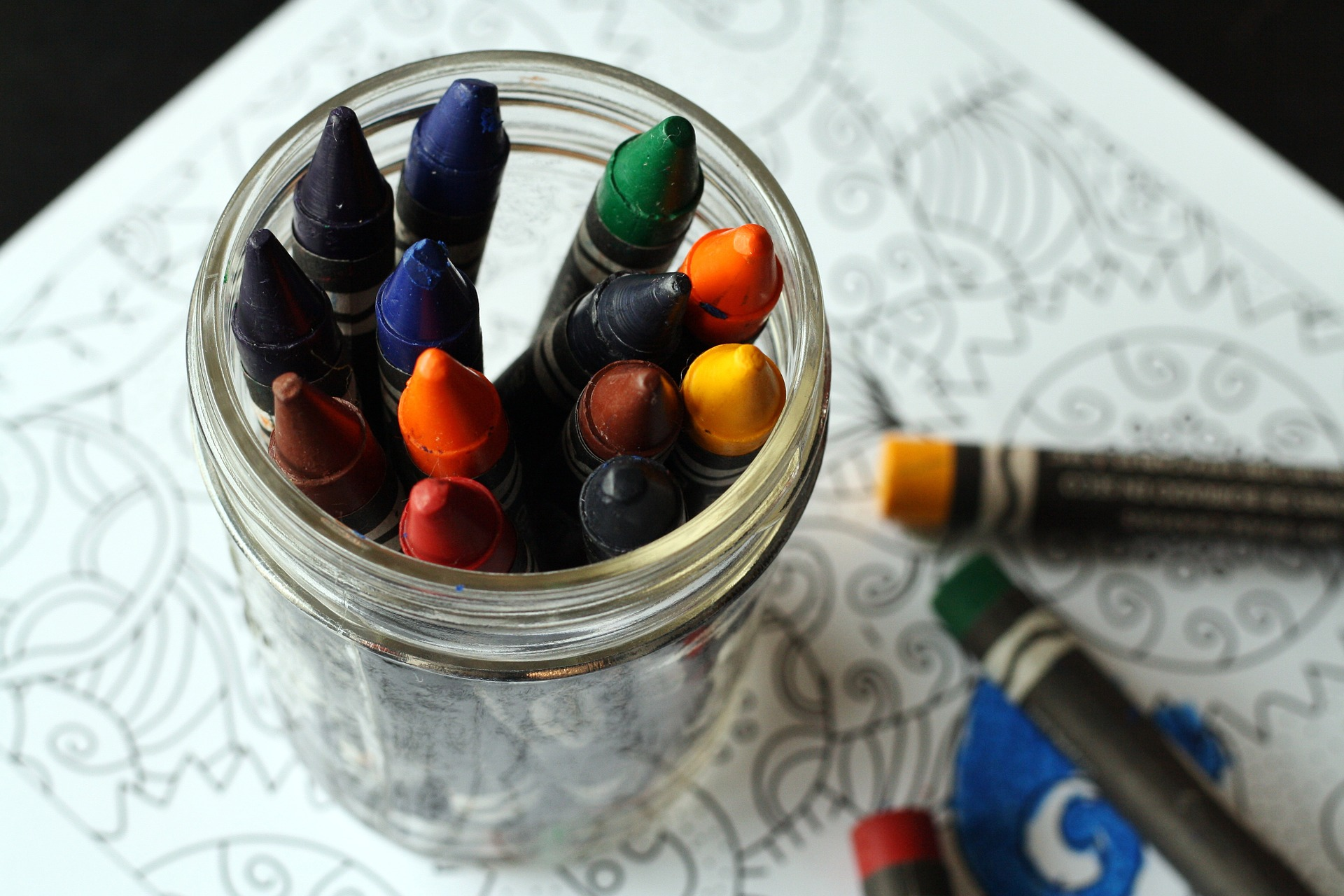 crayons in a jar on top of an adult coloring book