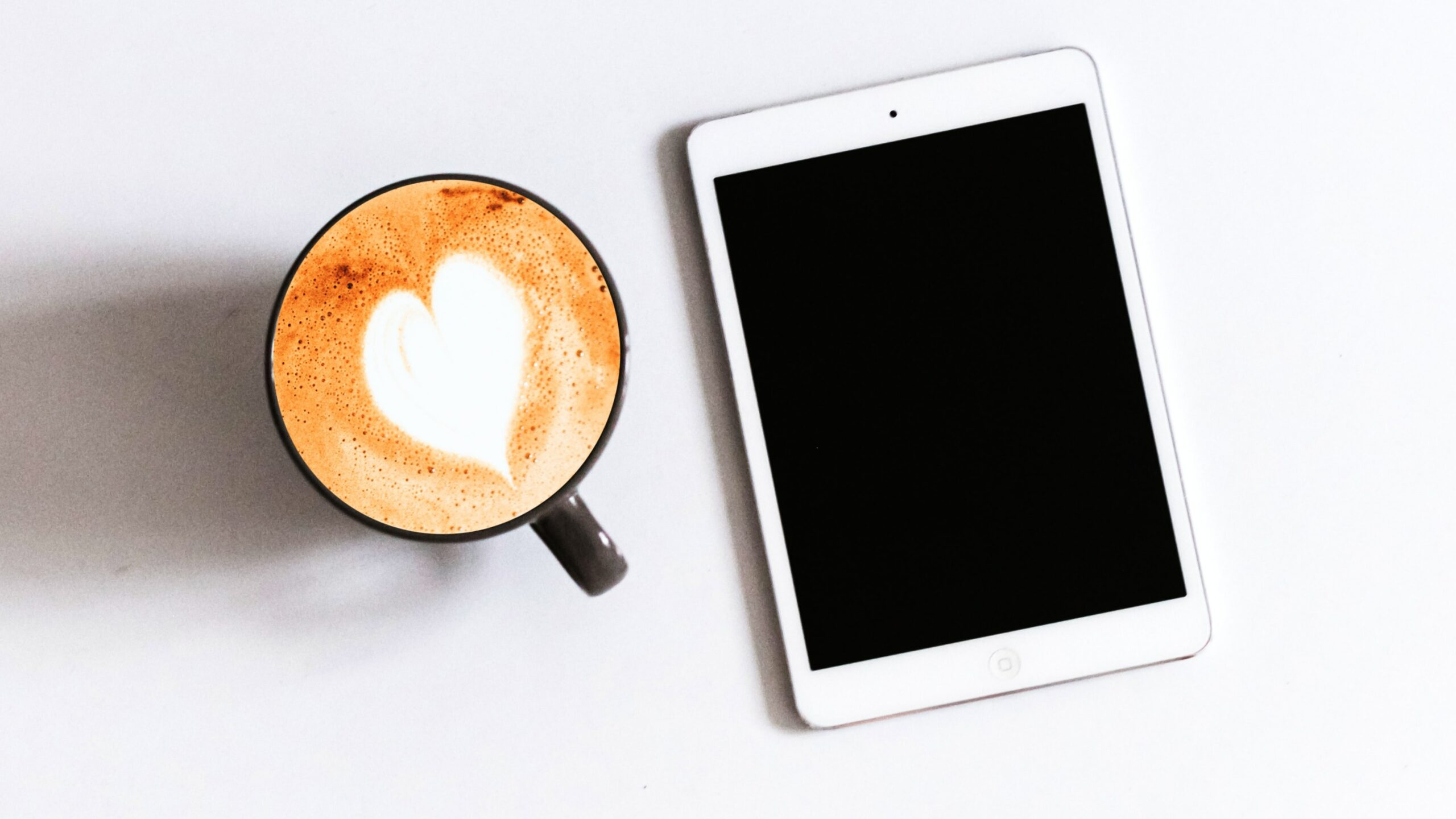 an iPad besides a cup of latte