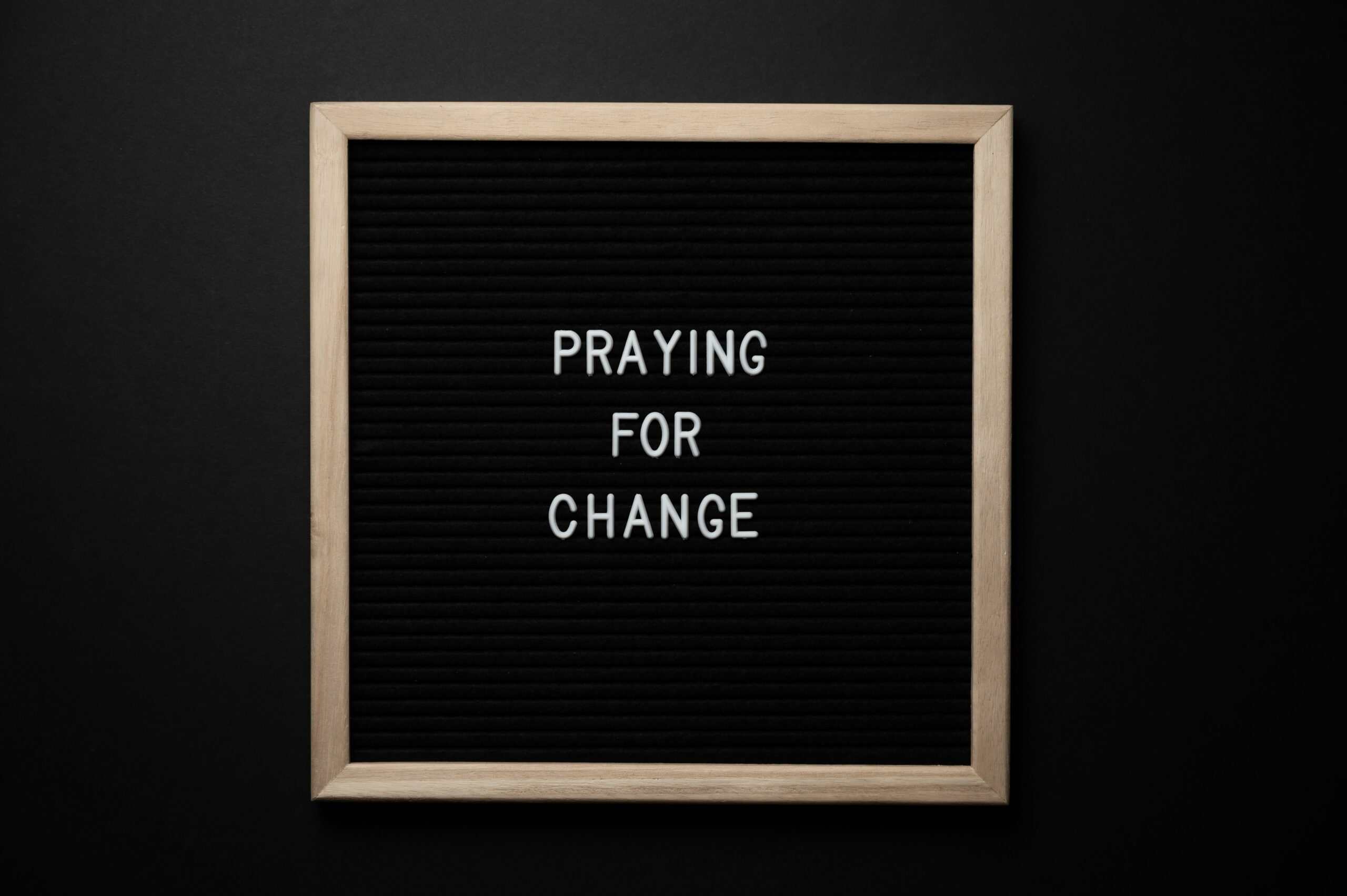 """the phrase """"praying for change"""" within a frame"""