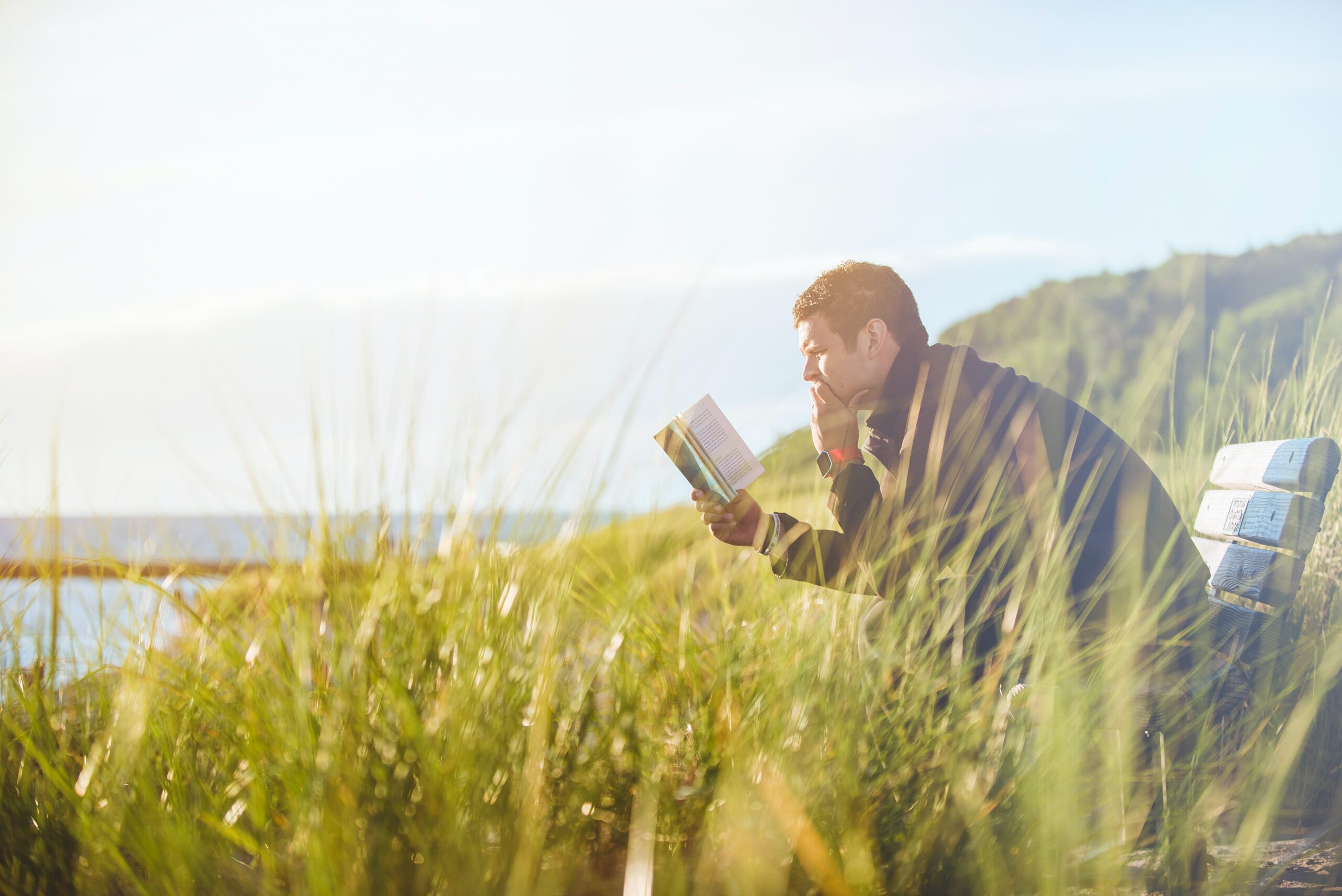 a man reading a book by a lake