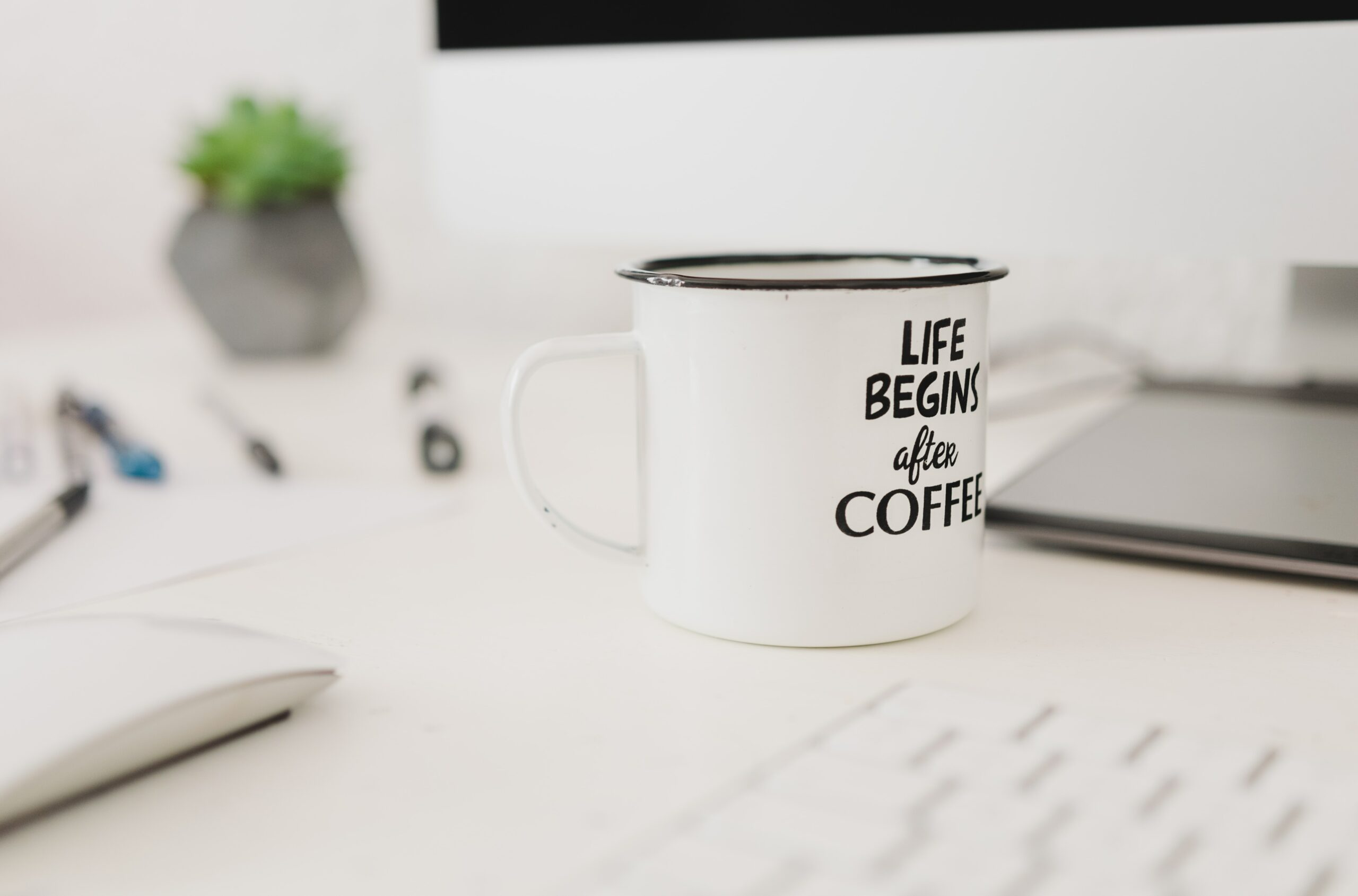 a cup of coffee on a computer desk