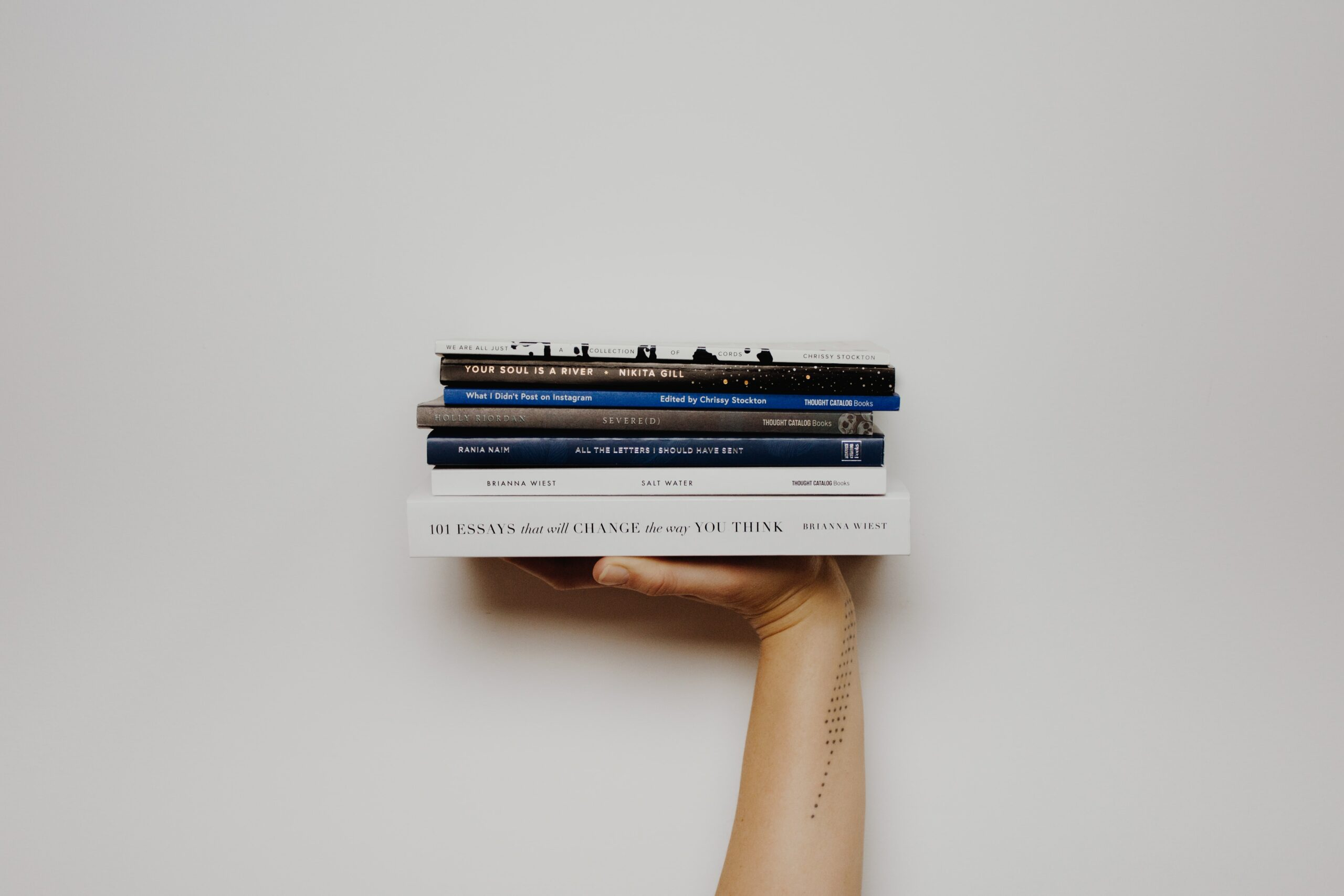 a pile of book on top of a hand